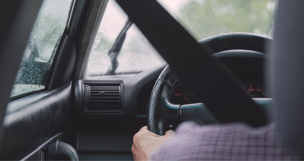 man-driving-auto-with-seatbelt-on-raining