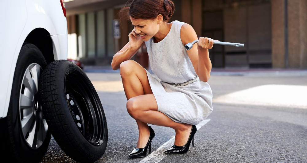 businesswoman-on-cell-phone-with-a-flat-tire