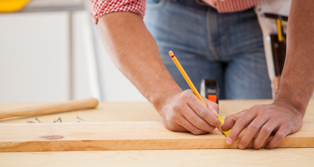 construction-worker-measuring-a-wood-board