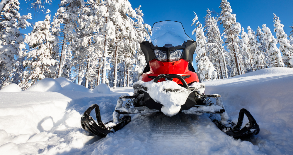 front-of-red-snowmobile-in-snow-with-snow-covered-trees