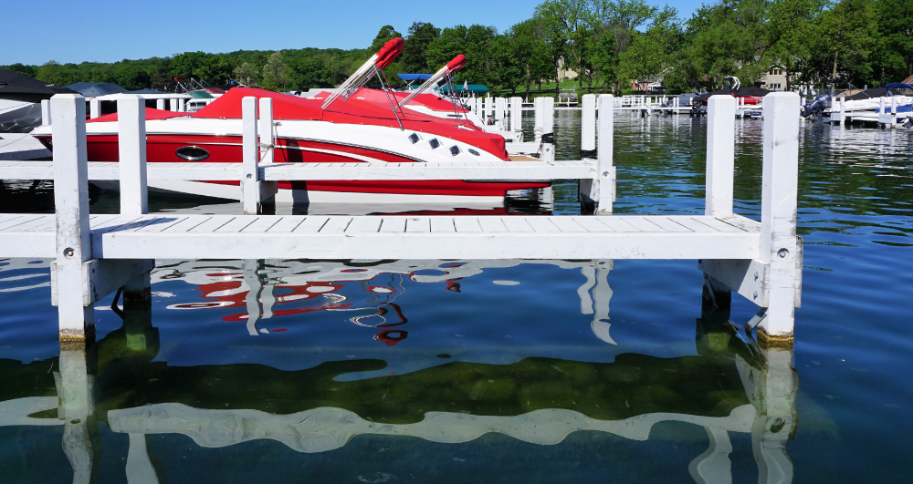red-speedboat-docked-on-lake-with-blue-sky